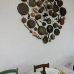 il grande cuore che caratterizza una parete del locale è stato realizzato con stoviglie e utensili di rame di recupero.