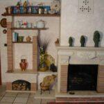 Caminetto con parete in travertino e cotto Rustici del Trusco